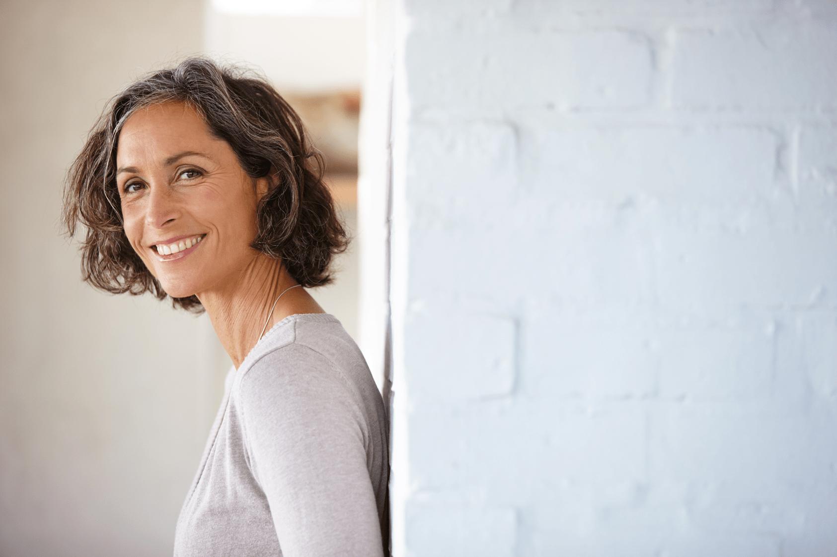 Wechseljahre Verstopfung Frau mittleren Alters an Wand gelehnt