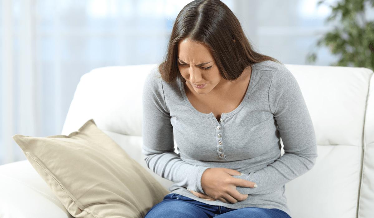 Verstopfung was tun Frau fasst sich mit schmerzverzerrtem Gesicht an den Bauch