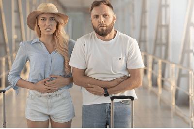 Verstopfung im Urlaub: Paar mit gepackten Koffern fasst sich an den Bauch