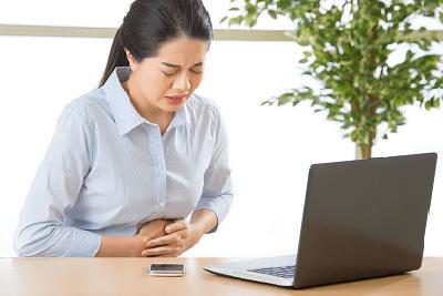Verstopfung durch Stress - Business-Frau fasst sich an den Bauch
